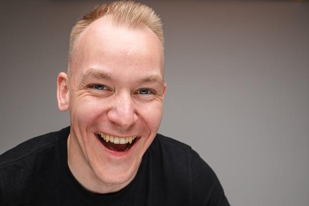 Foto de close-up de um homem caucasiano animado, sorrindo amplamente e rindo
