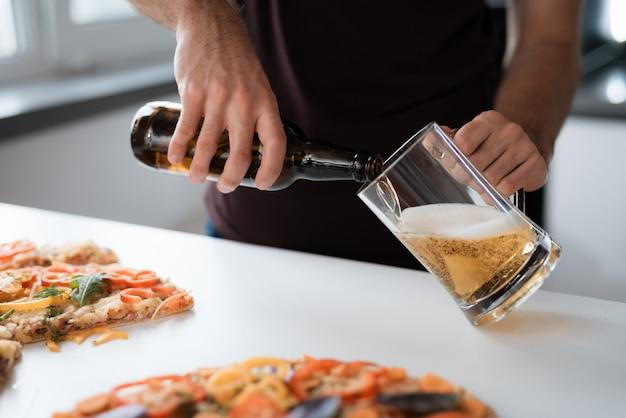 Foto de close-up de um homem derrama cerveja em um copo.