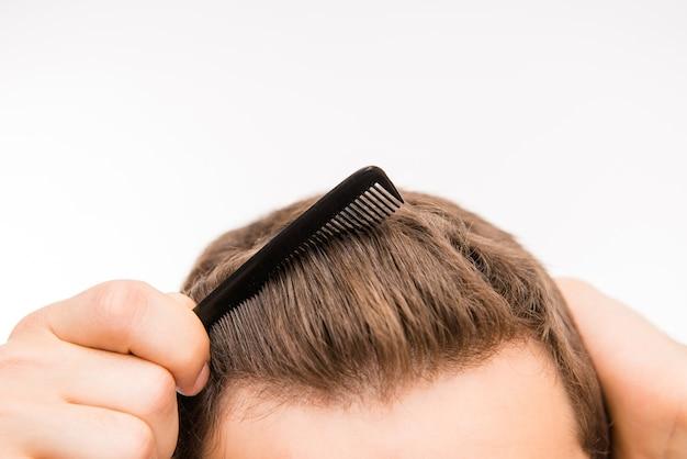 Foto de close-up de um homem escovando o cabelo