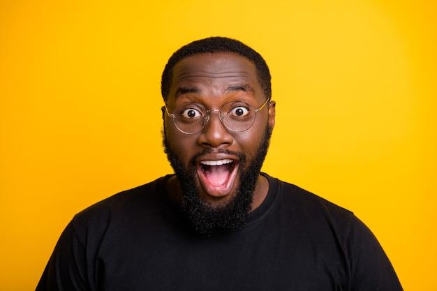 Foto de close-up de um homem extático e exultante regozijando-se com as vendas que começaram com entusiasmo no rosto gritando com óculos em uma camiseta isolada de cor vibrante