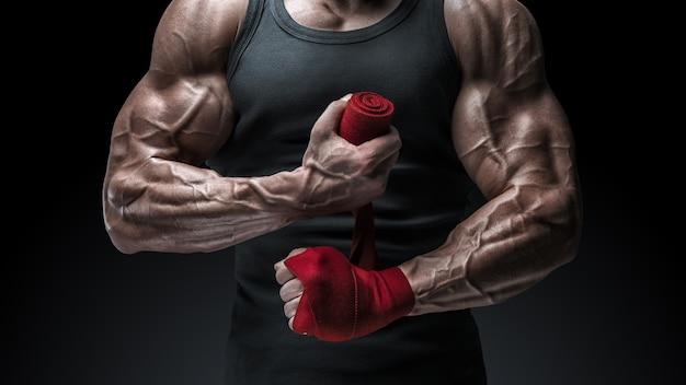 Foto de close-up de um homem forte envolvendo as mãos. mãos e punhos fortes, prontos para o treinamento e exercícios ativos. o homem está envolvendo as mãos com envoltórios de boxe vermelhos isolados no fundo preto