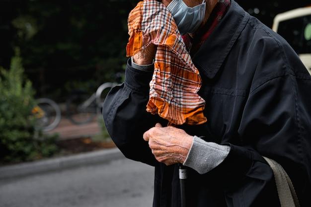 Foto de close-up de um homem velho enxugando o rosto com um lenço