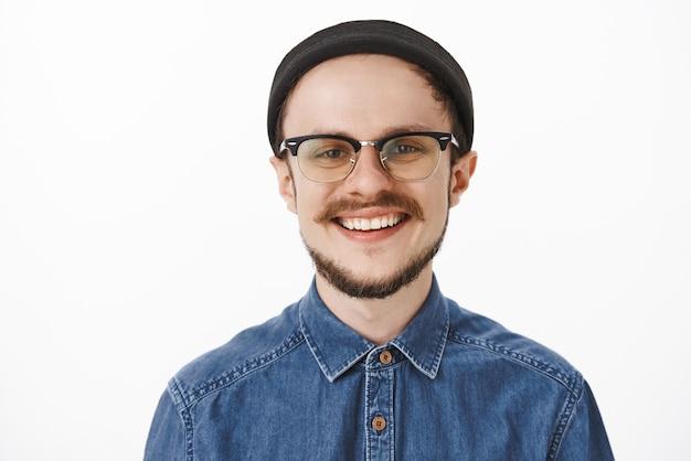 Foto de close-up de um jovem barbudo encantador encantado, com bigode nos óculos e gorro preto da moda, sorrindo alegremente e rindo, sentindo-se satisfeito e com sorte