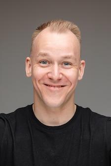 Foto de close-up de um simpático homem louro sorrindo enquanto posa