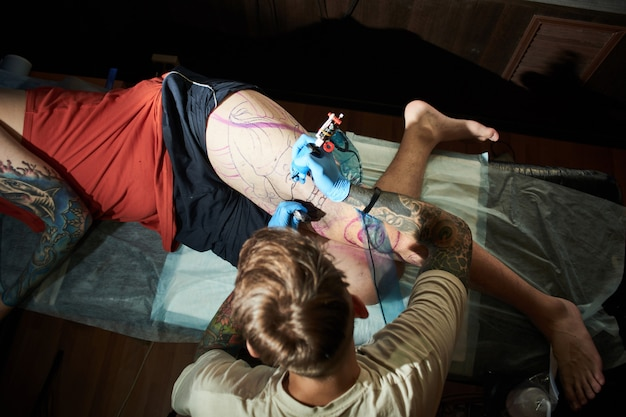 Foto de close-up de um tatuador barbudo profissional tatuando um cliente para um homem em um salão de beleza