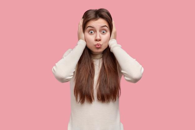 Foto de close-up de uma adorável jovem de cabelos escuros fazendo careta, fazendo beicinho, tapando os ouvidos com as duas mãos, não ouve nada