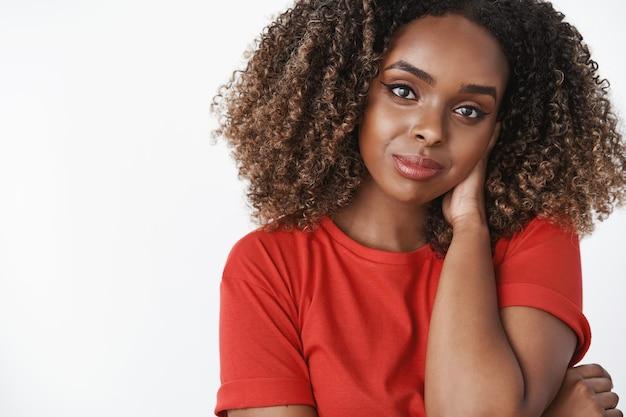 Foto de close-up de uma amiga afro-americana romântica e gentil, usando uma camiseta casual vermelha, tocando a nuca tímida e linda cabeça inclinando-se, sorrindo sensualmente com olhar sedutor sobre a parede branca