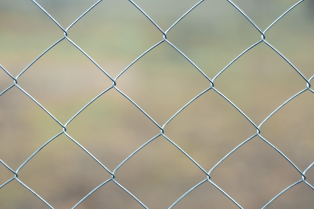 Foto de close-up de uma cerca de arame cinza em um fundo desfocado