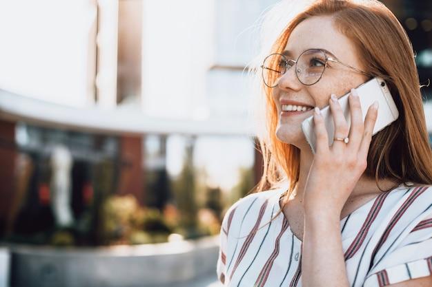 Foto de close-up de uma empresária caucasiana, ruiva, sardas e óculos, falando ao telefone com alguns clientes