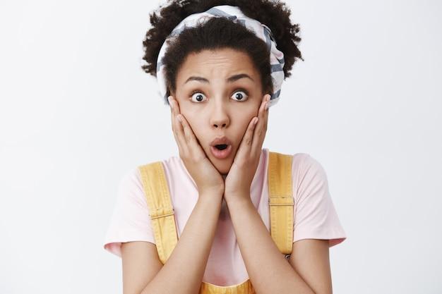 Foto de close-up de uma encantadora jovem afro-americana chocada e emocionada com uma faixa sobre o cabelo encaracolado e um macacão amarelo, arquejando, dobrando os lábios de espanto, olhando impressionada