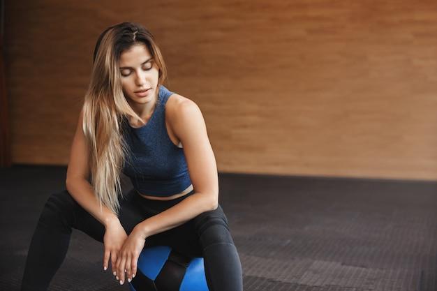 Foto de close-up de uma esportista vestindo roupas esportivas senta-se em uma bola de medicina