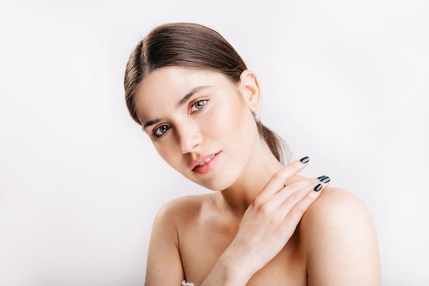 Foto de close-up de uma jovem encantadora com a pele limpa perfeita, sorrindo suavemente na parede branca.