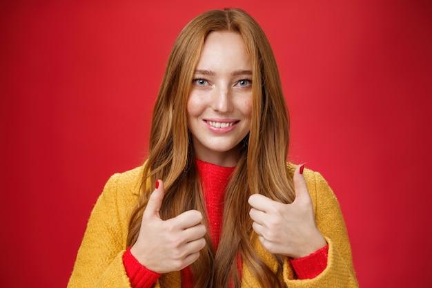 Foto de close-up de uma jovem feliz 20 anos satisfeita com casaco amarelo mostrando os polegares para cima gesto em gosto e aprovação dando feedback positivo, apreciando o belo evento em pé sobre fundo vermelho, sorrindo fofo.