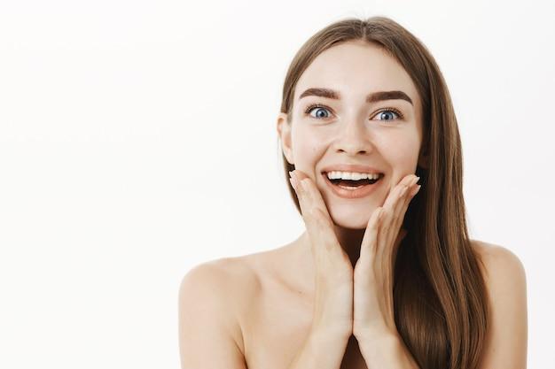 Foto de close-up de uma jovem impressionada e encantada, sorrindo amplamente, segurando as palmas das mãos no rosto e satisfeita com o resultado surpreendente após o produto cosmético aplicado na pele