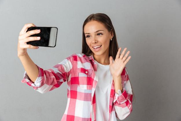 Foto de close-up de uma jovem mulher bonita, tirando foto de selfie por seus telefones