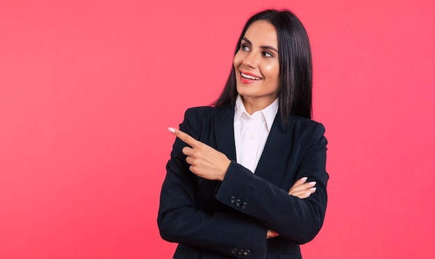 Foto de close-up de uma jovem mulher de negócios feliz, com longos cabelos negros, posando em um terno preto, olhando para a câmera e apontando para longe