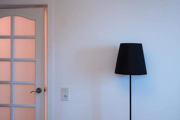 Foto de close-up de uma lâmpada de loft elegante na parte superior e na porta com interruptor de luz na sala perto da saída do apartamento