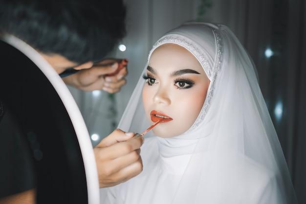 Foto de close-up de uma linda noiva muçulmana asiática com vestido de noiva branco e hijab maquiagem