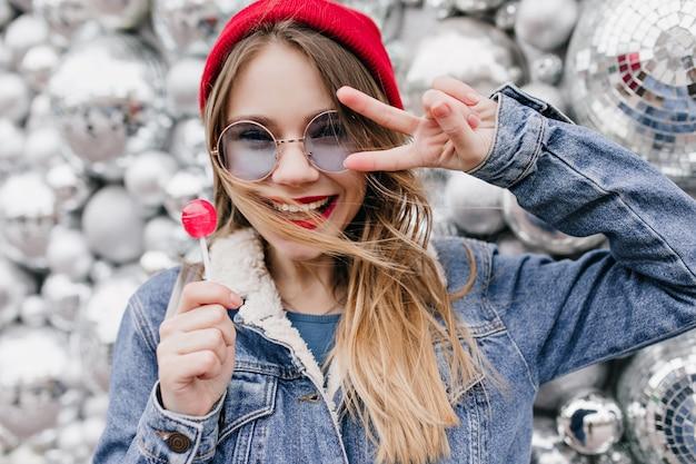 Foto de close-up de uma magnífica menina loira com expressão de rosto feliz, posando com bolas de discoteca. retrato de uma senhora bonita de chapéu vermelho, segurando o pirulito na parede urbana.