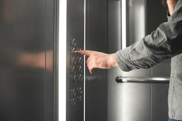 Foto de close-up de uma mão escolhendo um andar no elevador.