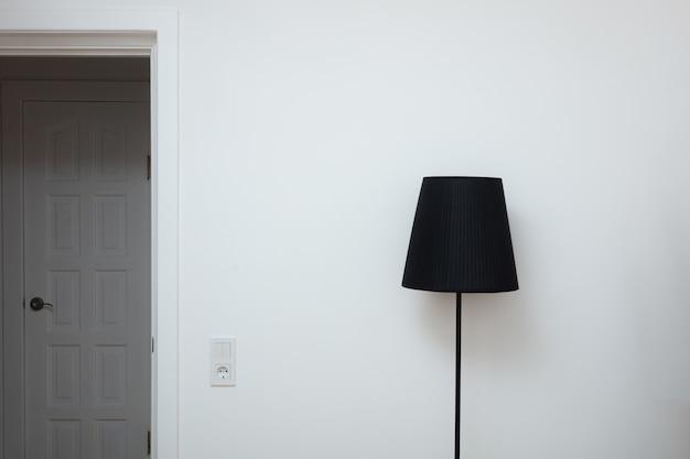 Foto de close-up de uma mão troca uma lâmpada em uma elegante lâmpada de loft na parte superior e na porta com interruptor de luz na sala perto da saída do apartamento