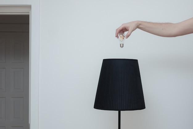 Foto de close-up de uma mão troca uma lâmpada em uma elegante lâmpada de loft na parte superior e o interruptor de luz na sala perto da saída do apartamento