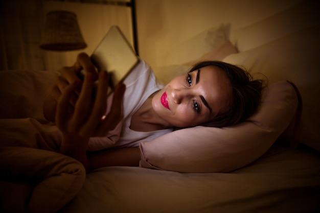 Foto de close-up de uma menina cansada, deitada em sua cama sob o cobertor, que está tendo problemas para dormir por causa de seu vício em internet.