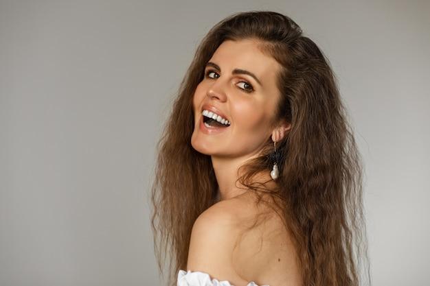 Foto de close-up de uma morena alegre com uma joia na orelha, rindo de algo engraçado. conceito de moda