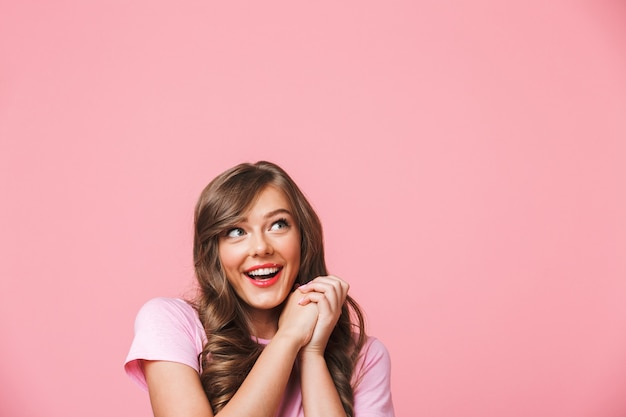 Foto de close up de uma mulher bonita alegre com cabelo castanho encaracolado comprido olhando de lado para copyspace e de mãos dadas em exultação, isolada sobre um fundo rosa