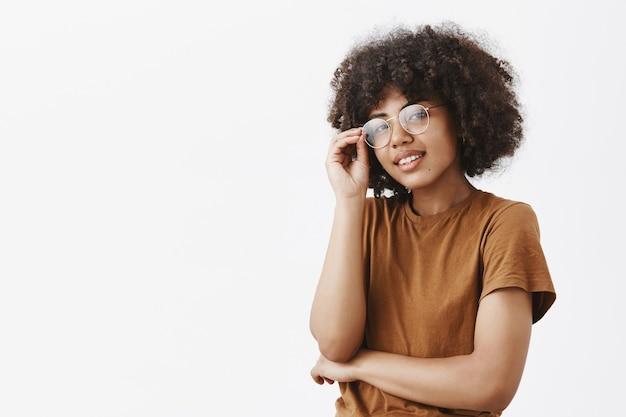 Foto de close-up de uma mulher bonita, elegante e moderna de pele escura tocando os óculos e olhando com uma expressão relaxada e satisfeita, tendo confiança em si mesma