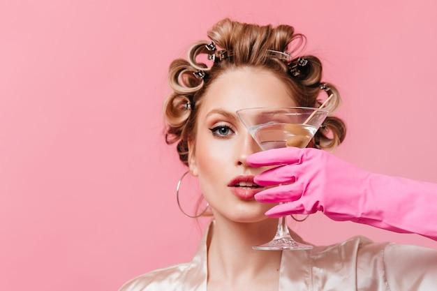 Foto de close-up de uma mulher loira cobrindo o rosto com uma taça de martini