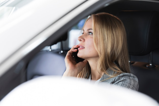 Foto de close-up de uma mulher loira falando ao telefone
