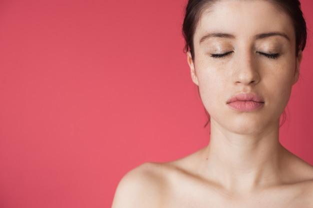 Foto de close-up de uma mulher sardenta com os olhos fechados posando com os ombros nus em uma parede rosa anunciando algo