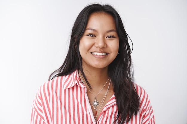Foto de close-up de uma mulher vietnamita atraente extrovertida e otimista em uma blusa listrada, rindo e sorrindo, expressando humor positivo e posando sobre fundo branco