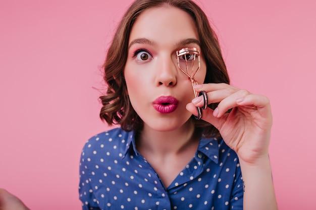Foto de close-up de uma senhora de olhos castanhos com expressão de surpresa curvando seus cílios. adorável garota caucasiana com cabelo curto, preparando-se para o encontro.