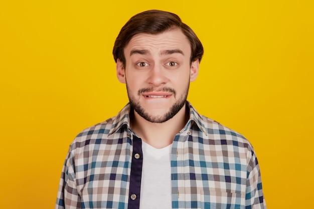 Foto de close-up de youn gman mordida lábios dentes preocupados falha problema camisa quadriculada roupa isolado amarelo brilhante fundo