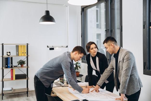 Foto de close-up do grupo de arquitetos desenhando o plano de construção juntos no escritório
