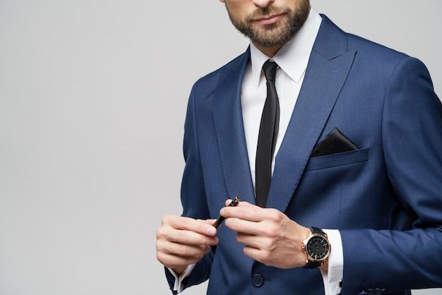Foto de close-up do jovem empresário vestindo terno segurando a caneta