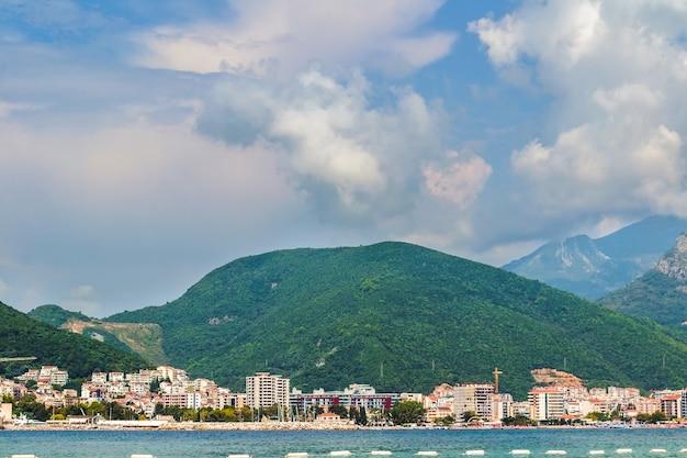 Foto de close-up do mar e da paisagem urbana no sopé das montanhas na costa em um dia brilhante. a antiga cidade marítima de budva em montenegro, na costa do mar adriático