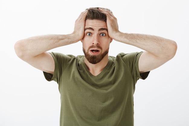 Foto de close-up do namorado desajeitado fofo e nervoso frustrado e hesitante não pode entrar em pânico de mãos dadas na cabeça em consternação e preocupação com a boca aberta sem saber o que fazer, perturbado por uma parede branca