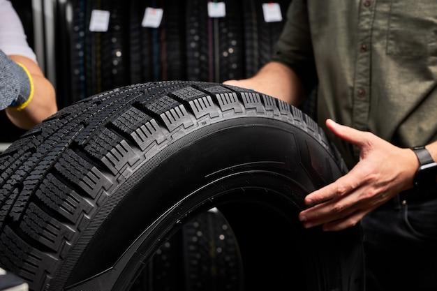Foto de close-up do pneu do carro, foco no pneu preto, cliente examinando a superfície e suas características antes de fazer a compra