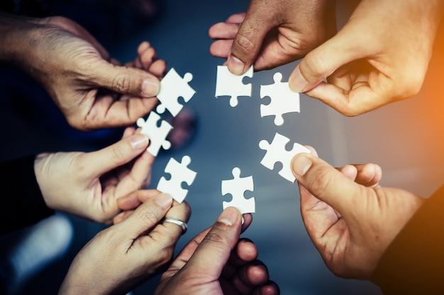 Foto de close-up dos empresários segurando o quebra-cabeça