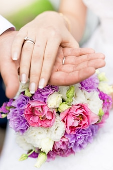 Foto de close-up em foco suave do noivo segurando a mão da noiva em um buquê de noiva