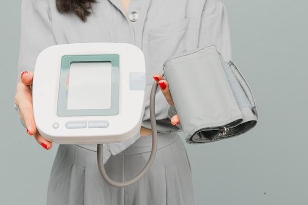 Foto de close-up feminina segurando um medidor de pressão, verificando a saúde do coração