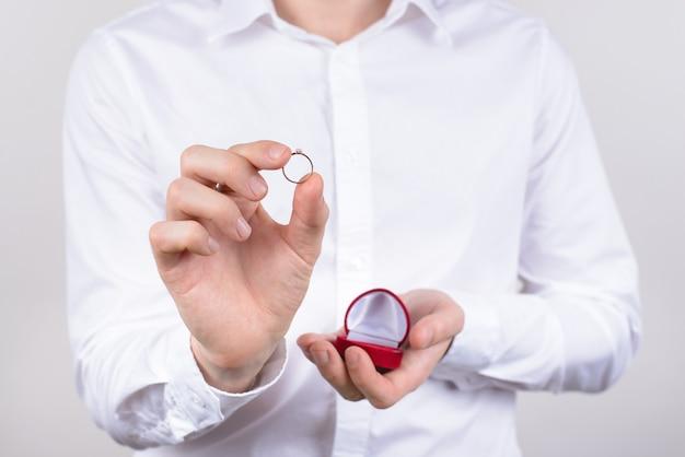 Foto de close up foto cortada de cara feliz, alegre, animado, feliz, otimista, positivo, segurando um pequeno anel na mão com dedos isolados em um fundo cinza