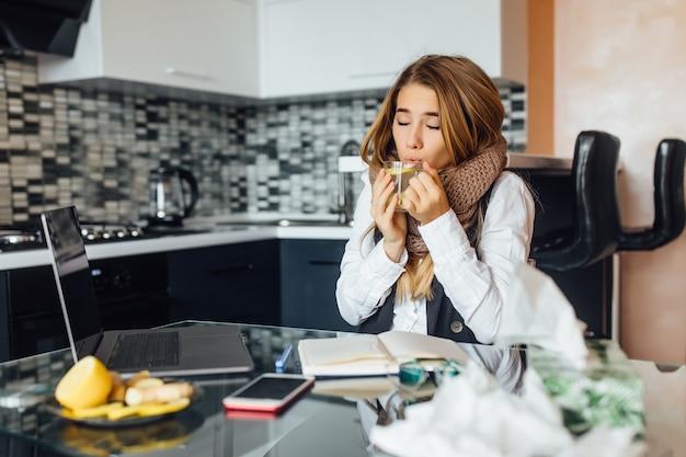 Foto de close-up, jovem doente com lenço quente, sentada na mesa da cozinha, segurando uma xícara com chá