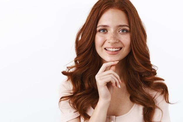 Foto de close-up, mulher ruiva feminina atraente com penteado longo encaracolado, sardas tocando o queixo pensativas, ponderando uma ideia curiosa, sorrindo intrigado e satisfeito, pensando sobre a parede branca