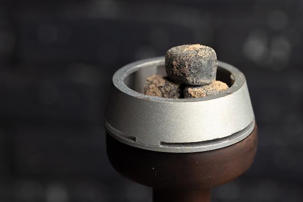 Foto de close up queimando carvão de narguilé na tigela de narguilé