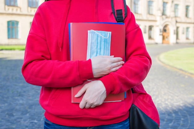 Foto de close-up recortada de adolescente inteligente em um macacão vermelho casual segurando cadernos e máscara médica nas mãos