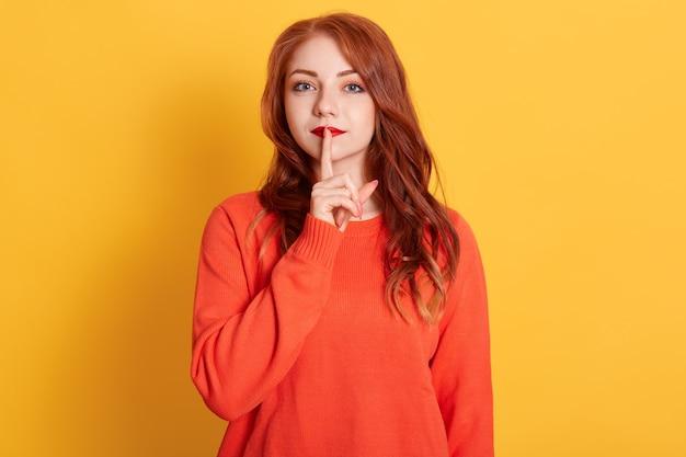Foto de close-up, senhora bonita com pomada vermelha, penteado longo vermelho, mantendo o dedo indicador perto da boca